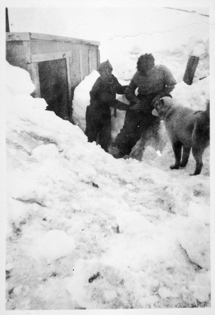 To menn utenfor en hytte som var en forlegning av hovedstasjonen