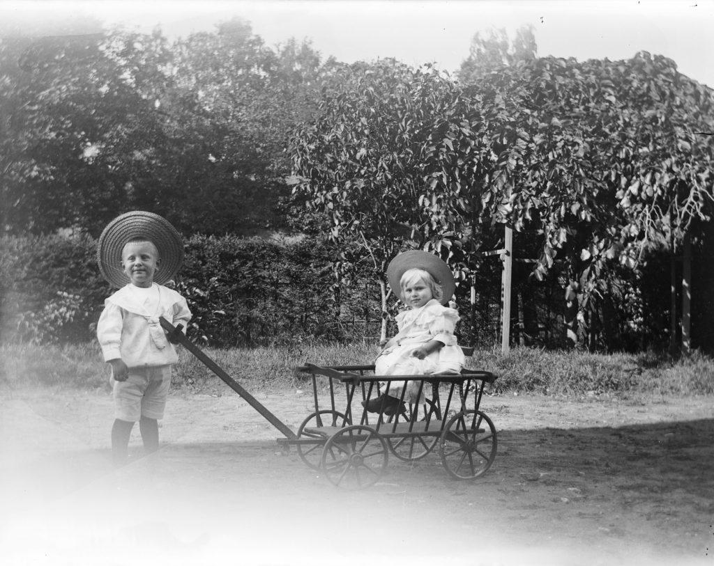 Ludvig Emil Hammer trekker vognen med sin bror, Olav Hammer på tunet på Solhaug i 1903