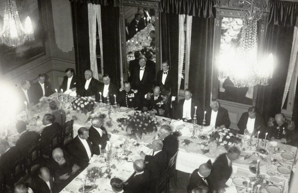 Kong Haakon, kronprins Olav, statsminister Nygaardsvold med flere under festmiddagen på Arendal rådhus 9. november 1935
